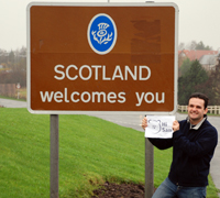 Hugh in front of welcome to Scotland road sign